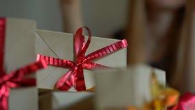 Verpackende Geschenke einer jungen Frau Geschenk eingewickelt im Kraftpapier mit einem Rot- und Goldband f?r Weihnachten oder neu stock footage