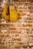 Verpackenhandschuhe, die an der Backsteinmauer hängen Stockfoto