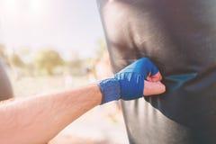 Verpackentraining des jungen Mannes Boxer-Übungs-athletisches Verpacken-Konzept Boxerdurchschlagshand durch Sandsack lizenzfreie stockbilder