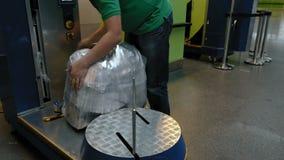 Verpackung der Gepäckgepäcktasche am Flughafenabfertigungsgebäude stock footage