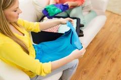 Verpackung der jungen Frau kleidet in Reisetasche Stockfotografie