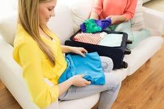 Verpackung der jungen Frau kleidet in Reisetasche Stockfotos