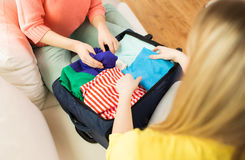 Verpackung der jungen Frau kleidet in Reisetasche Lizenzfreie Stockfotografie