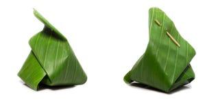 Verpackung des Kokosnussvanillepuddings mit klebrigem Reis Setzen Sie grüne Bananenblätter Auf einem weißen Hintergrund mit Absch Stockfoto