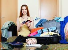 Verpackungsdokumente der jungen Frau in Koffer Stockbilder