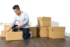 Verpackungspappe Haus des jungen asiatischen Mannes bewegliche unter Verwendung des Klebers Stockfotos