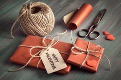 Verpakte gift met markering ` Gelukkig Valentine `, bruin koord, verpakkend document, schaar en decoratieve harten stock foto's