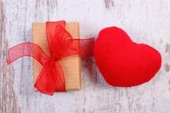 Verpakte gift voor Valentijnskaartendag en rood hart op oude houten plank Stock Foto