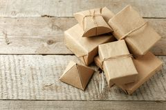Verpakte Kerstmis stelt in document ambachtpakket voor op uitstekende houten achtergrond, exemplaarruimte modieuze giften, seizoe royalty-vrije stock afbeeldingen