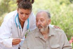 Verpleegster of arts en hogere patiënt stock foto