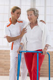 Verpleegster Assisting Senior Woman om met Zimmer te lopen stock foto
