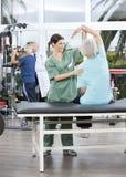 Verpleegster Assisting Senior Woman in Wapenoefening in Rehab-Centrum royalty-vrije stock fotografie