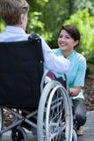 Verpleegster die aan bejaarde op rolstoel glimlachen Stock Fotografie