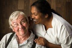 Verpleegster die aan bejaarde spreken stock foto