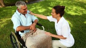Verpleegster die aan de mens in rolstoel buiten spreken stock video