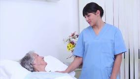 Verpleegster die aan een hogere vrouw in haar bed spreken stock footage