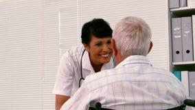 Verpleegster die aan een oude mens in een rolstoel spreken stock videobeelden