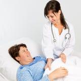 Verpleegster die aan hogere patiënt helpt royalty-vrije stock afbeelding
