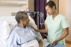 Verpleegster die aan Hogere Vrouw spreekt stock afbeeldingen
