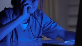 Verpleegster die aan laptop en sprekende telefoon, de beheerder van het ziekenwagencall centre werken stock videobeelden