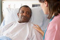 Verpleegster die aan Mannelijke Patiënt op Afdeling spreken Stock Fotografie