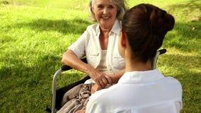 Verpleegster die aan vrouw in rolstoel buiten spreken stock footage