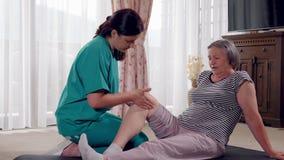 Verpleegster die beenmassage geven aan hogere vrouw in een pensioneringshuis stock videobeelden
