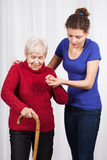 Verpleegster die bejaarde damegang helpen Stock Foto's