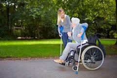 Verpleegster die bejaarde helpt stock afbeeldingen
