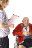 Verpleegster die bejaarde patiënt controleert Stock Afbeelding