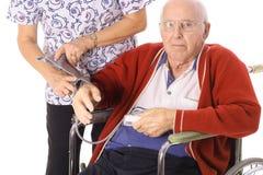 Verpleegster die bejaarde patiëntenbloeddruk controleert royalty-vrije stock afbeelding