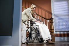 Verpleegster die bejaarde in rolstoel thuis helpt royalty-vrije stock foto's