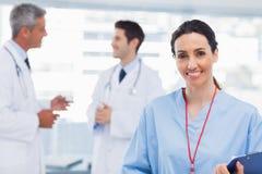 Verpleegster die bij camera glimlachen terwijl de artsen samen spreken royalty-vrije stock afbeeldingen