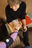 Verpleegster die bloeddruk van bejaarde neemt. Royalty-vrije Stock Foto