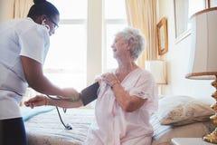 Verpleegster die bloeddruk van een hogere vrouw controleren Royalty-vrije Stock Fotografie