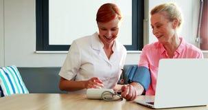 Verpleegster die bloeddruk van hogere patiënt controleren stock footage