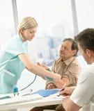 Verpleegster die bloeddruk van oude patiënt meet Royalty-vrije Stock Afbeeldingen