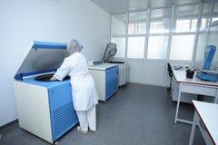 Verpleegster die containers met bloed plaatsen in een centrifuge stock fotografie