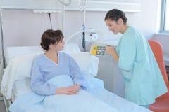Verpleegster die de geduldige controles van het het ziekenhuisbed tonen royalty-vrije stock foto's