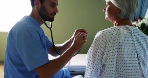 Verpleegster die de patiënt met stethoscoop controleren stock footage