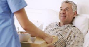 Verpleegster die dienblad met ontbijt geven bij de hogere mens stock videobeelden
