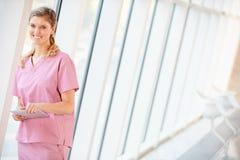 Verpleegster die Digitale Tablet in Gang van het Moderne Ziekenhuis gebruiken Royalty-vrije Stock Afbeeldingen