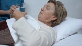 Verpleegster die dosis antibiotica geven aan vrouwelijke patiënt na verrichting, het ziekenhuis stock video