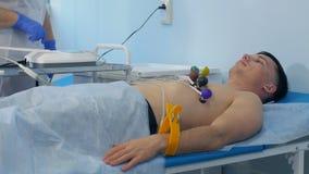 Verpleegster die ECG op een mannelijke patiënt uitvoeren Stock Afbeeldingen