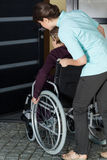Verpleegster die een gehandicapte vrouw helpen om het huis in te gaan Stock Fotografie