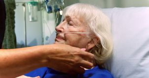 Verpleegster die een hogere patiënt in de afdeling 4k onderzoeken stock video