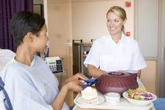 Verpleegster die een Patiënt dient een Maaltijd in Haar Bed stock foto