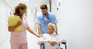 Verpleegster die een patiënt in een rolstoel duwen terwijl het spreken aan een arts stock footage