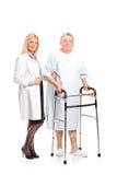Verpleegster die een patiënt helpt om een leurder te gebruiken Stock Fotografie