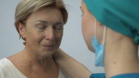Verpleegster die en ondersteunend bejaarde vrouwelijke patiënt met fatale ziekte, gezondheid koesteren stock videobeelden